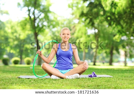 Young female fitness instructor sitting in park