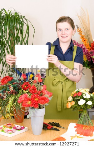 Young female florist holding white sign - stock photo