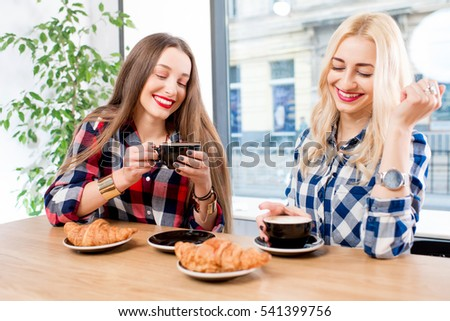 Young female friends dressed casually in checkered shirts sitting with coffee cups and croissants at the cafe