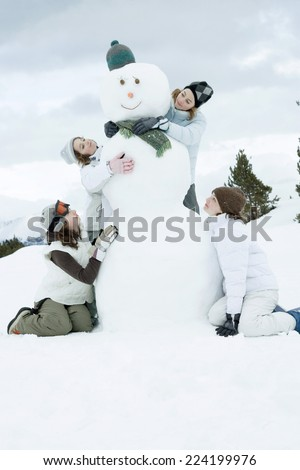 Young female friends grouped around snowman - stock photo