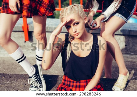 Young female friends having fun outdoors. Girl braids cornrows her girlfriend. Lifestyle - stock photo