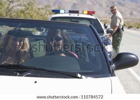 Young female friends reading ticket with traffic officer standing in the background