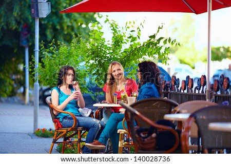 young female friends sitting on cafe terrace, urban outdoors - stock photo