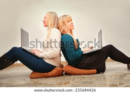 young female friends with laptop computers surfing the internet  enjoying social networking modern times connected lifestyle concept - stock photo