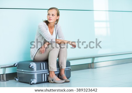 Young, female frustrated passenger at the airport, waiting desperately for her delayed flight (color toned image; shallow DOF) - stock photo