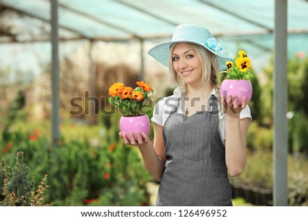 Young female gardener holding flower pots in a garden - stock photo