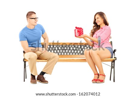 Young female giving a gift box to her boyfriend, seated on a bench, isolated on white background - stock photo
