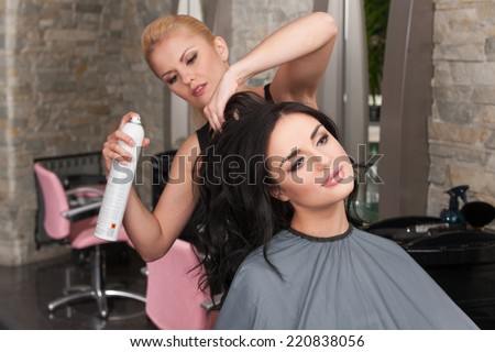 Young female hairdresser applying spray on client's hair. Female hairdresser works on woman hair in salon  - stock photo
