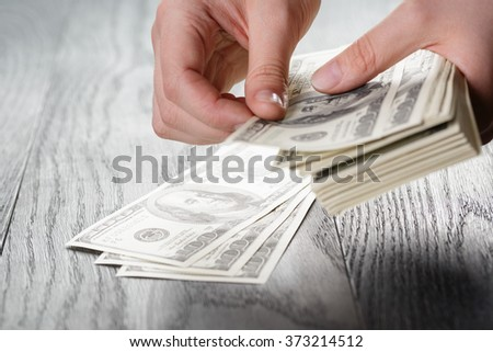 young female hands count dollar bills on wood table - stock photo