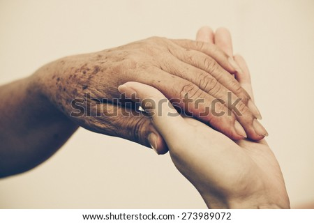 Young female hands touching old female hand - taking care of the elderly concept - stock photo