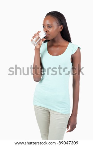 Young female having a sip of water against a white background