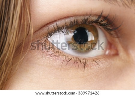 young female hazel eye with contact lens, macro photo