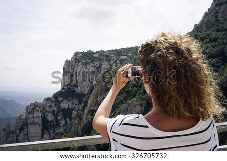 Young female hiker taking photo with smart phone at mountain peak
