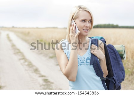 Young female hiker using mobile phone while standing on field - stock photo