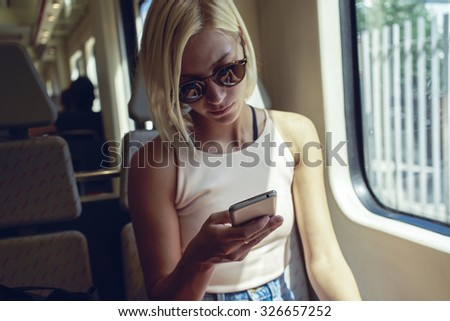 young female hipster writes a message in a moving train - stock photo