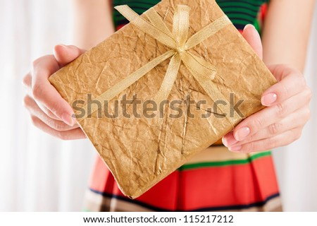 Young female holding a book wrapped in golden paper with ribbon bow - stock photo