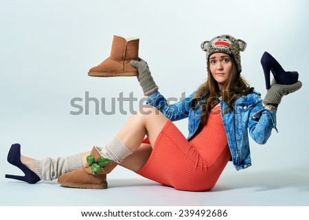 Young female holding a boot one hand and high heels another one - stock photo