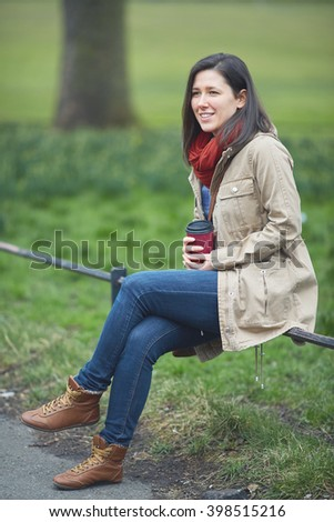 Young female holding her coffee cup while sitting on the park railing - stock photo