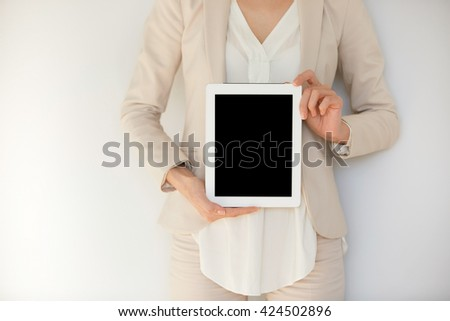 Young female holding tablet computer isolated against white studio wall. Businesswoman showing tablet with blank copy space screen for your slogan or text message. Technology and communication content - stock photo