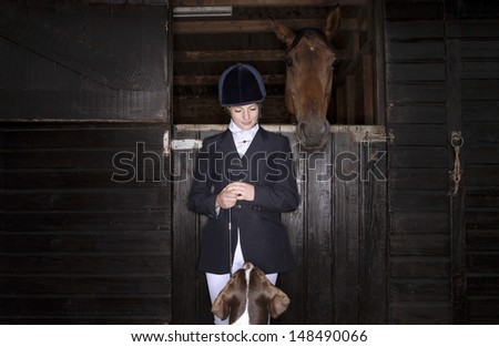 Young female horseback rider with horse and dog in the stable - stock photo