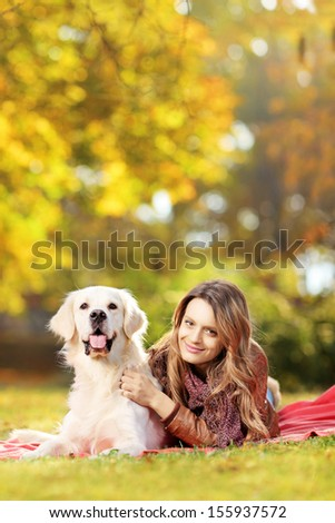 Young female in a park with her labrador retriever dog  - stock photo