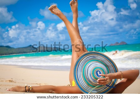 Young female in beautiful summer hat enjoying the perfect summer day on tropical beach. Summer luxury vacation. Holidays on Waimanalo Beach Park on the beautiful Hawaiian Island of Oahu - stock photo