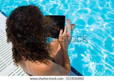 Young female in black swimsuit looking her photos on touch pad while relaxing near pool in sunny summer day, brunette woman holding digital tablet with blank copy space screen for your advertising  - stock photo