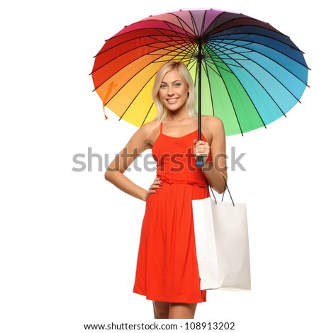 Young female in bright red dress standing under rainbow umbrella and holding shopping bag, over white background