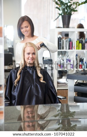 Young Female in hair salon having her hair styled - stock photo