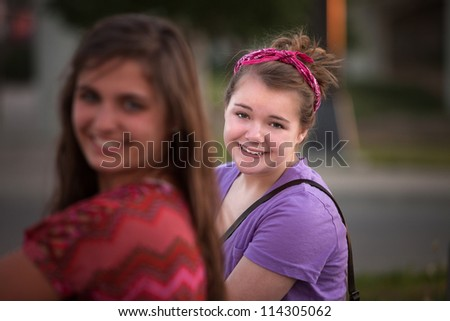 Young female in purple with friend outdoors - stock photo