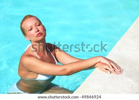 Young female in white bikini  enjoying sun in swimming pool - stock photo