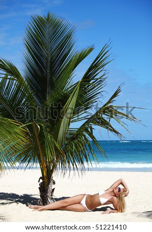Young female in white bikini enjoying sunny day under palm tree on the tropical beach - stock photo