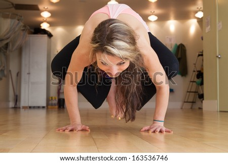 young female in yoga studio doing yoga poses - stock photo