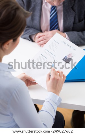 Young female interviewer checking elderly man's curriculum vitae - stock photo