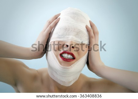 Young female is screaming in pain after her plastic surgery with really dark lipstick on her lips. Against blue background and vignette. - stock photo