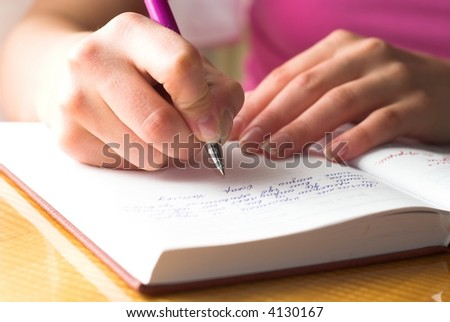 Young female is writing notes and planning her schedule.