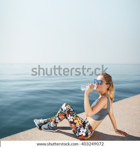 Young female jogger drinking water sitting on the beach after hard running work out drinking water out of a plastic bottle. Beautiful blond woman in sunglasses and sportswear relaxing. Fitness concept - stock photo