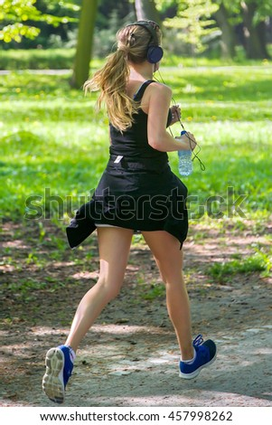 Young female jogger with headphones - stock photo