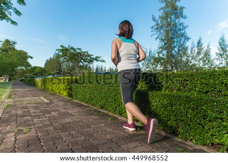 Young female jogging in park at morning