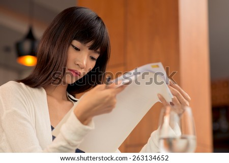 Young female lawyer carefully reading contract