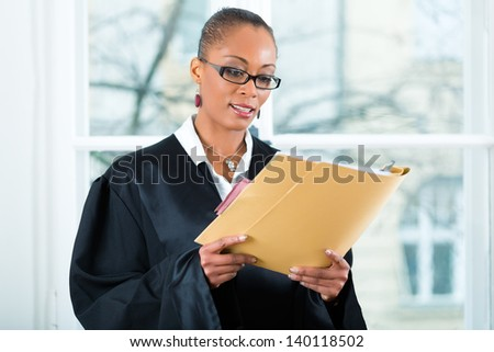 Young female lawyer working in her office with a file or dossier - stock photo