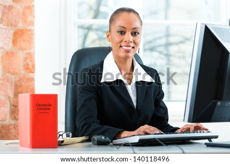 Young female lawyer working in her office with a typical law book and writing on the Computer - stock photo