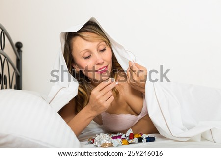 Young female laying in bed with sweets in secret