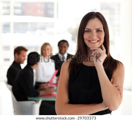 Young Female leader in standing in front of team - stock photo
