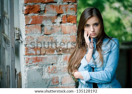 young female leaning against the wall outdoors wearing a jean jacket looking at camera - stock photo