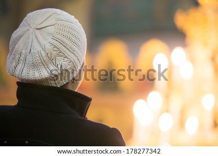 Young female looking at candle flames in church during praying - stock photo