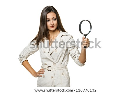 Young female looking through magnifying glass at the blank copy space, over white background - stock photo