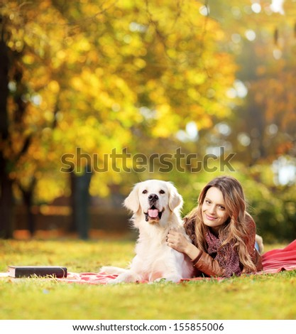 Young female lying down with her labrador retriever dog in a park, shot with a tilt and shift lens