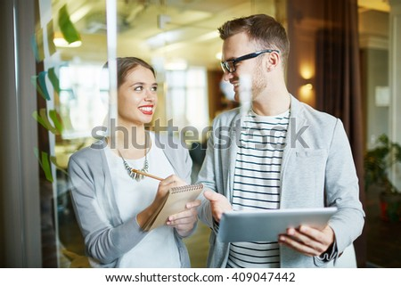 Young female manager consulting with her experienced male colleague - stock photo