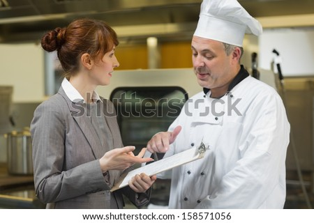 Young female manager talking to the head cook standing in a professional kitchen - stock photo